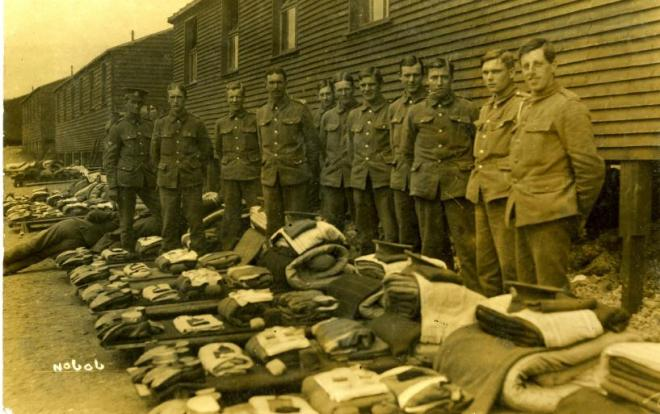 Men of 9th Battalion outside a camp hut awaiting a kit inspection at Shoreham Camp, 1915