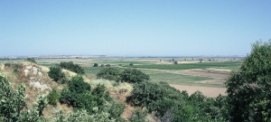The view from the hill of Hisarlik, thought to be the site of Homer's Troy. (2010) Across the plain, much of which would have been a sea bay in the Bronze Age, the southern entry to the Dardanells can be glimpsed on the horizon to the right, and the Aegean Sea to the left.