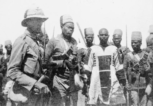Emir Mahmud wearing Mahdist patched jibba, bloodstained from a wound in the left leg, escorted by a British officer and men of the 10th Sudanese Regiment © Imperial War Museum  IWM (HU 93852)
